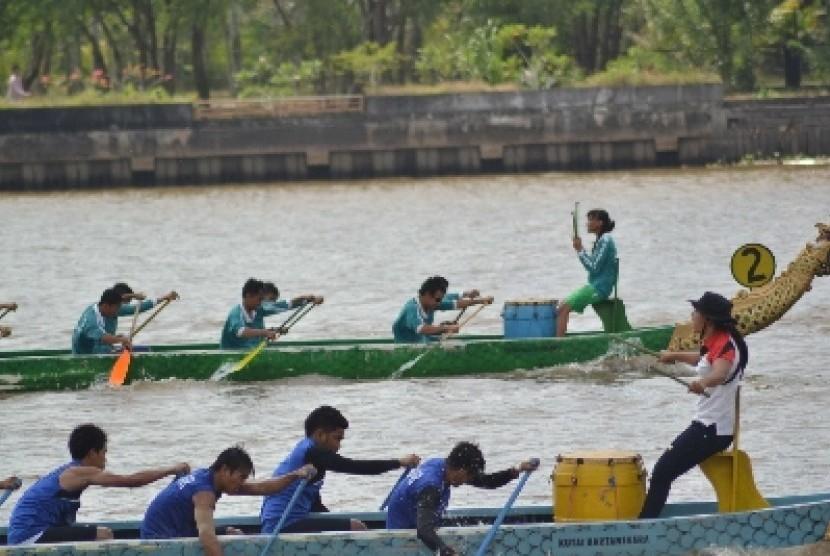 . Seorang pemandu terus memberi semangat anggota timnya untuk memukul bedug pada lomba perahu naga dalam Festival Erau Adat Pelas Benua Etam.