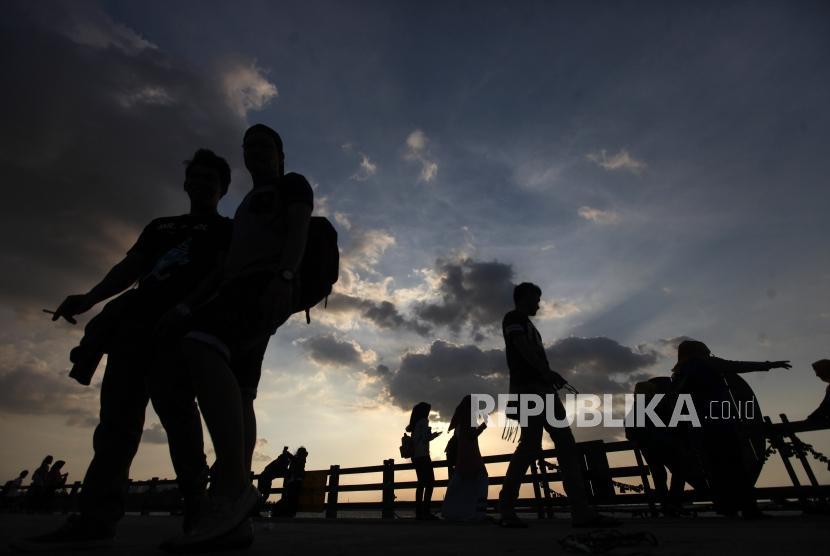 Pengunjung menikmati suasana pantai saat liburan di Pantai Ancol, Jakarta, Jumat (30/3).