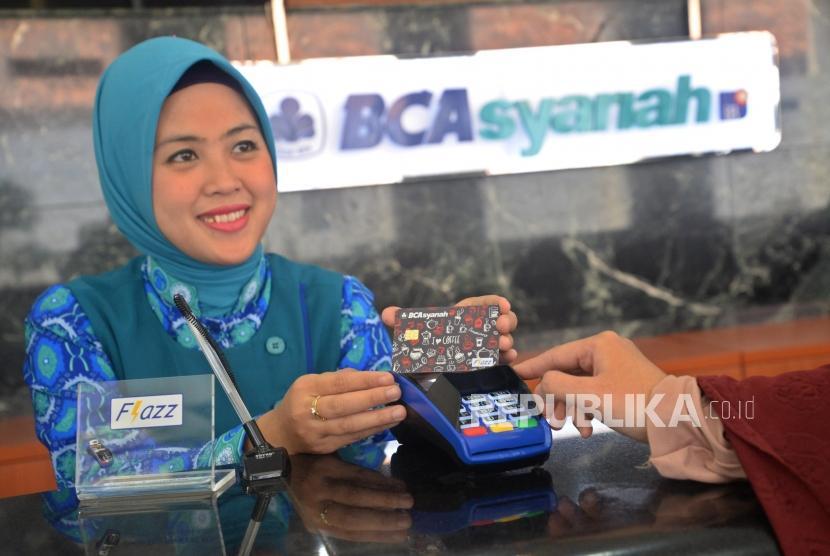 Petugas melayani kartu BCA Syariah di kantor cabang, Jakarta, Selasa (14/11).