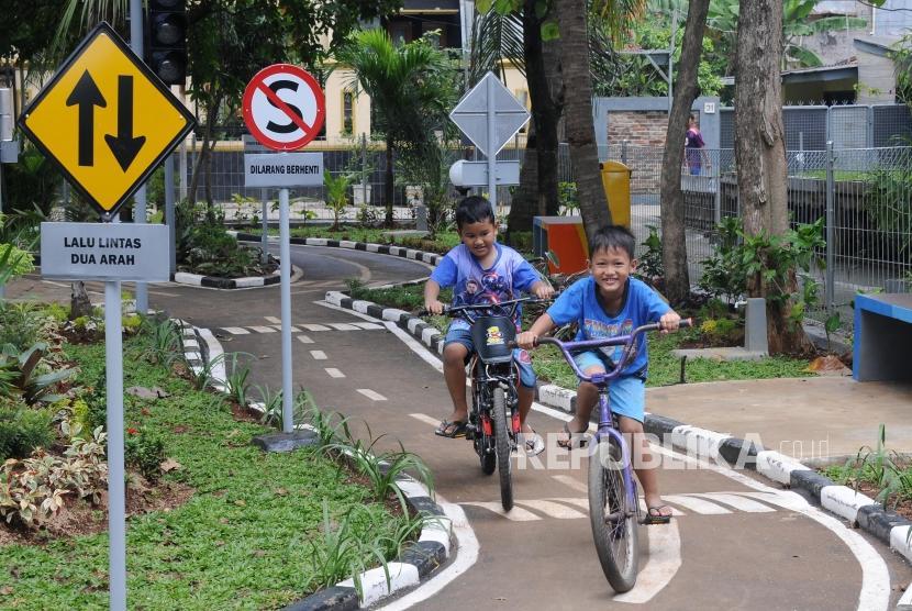 Anak-anak bermain sepeda di taman lalu lintas RPTRA Kebon Pala, Jakarta, Selasa (27/2).