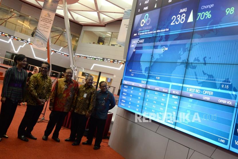 Asuransi Syariah Pertama di BEI. Menteri Koperasi dan UKM Anak Agung Ngurah Puspayoga (tengah) bersama Direktur BEI Kiki Widyasari, Direktur BEI Samsul Hidayat, Komisaris Utama Asuransi Jiwa Syariah Jasa Mitra Abadi (JMA) Mochamad Andy Arslan Djunaid, dan Direktur Industri Keuangan Non Bank Syariah Otoritas Jasa Keuangan (OJK) M Muchlasin (dari kiri) melihat pergerakan harga saham Asuransi Jiwa Syariah JMA usai pencatatan perdana di BEI, Jakarta, Senin (18/12).