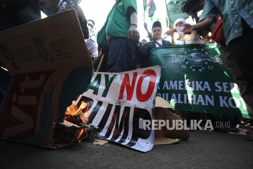 Pembakaran. Peserta aksi melakukan pembakaran bendera poster  bertuliskan say no trump dalam  aksi damai di depan kantor Kedutaan Amerika Sertikat, Jakarta, Jumat (08/12).