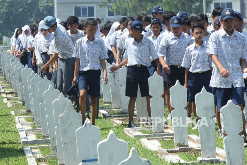Puluhan pelajar berjalan di antara deretan makam pahlawan pada peringatan Hari Pahlawan, di Taman Makam Pahlawan Cikutra, Kota Bandung, Jumat (10/11).