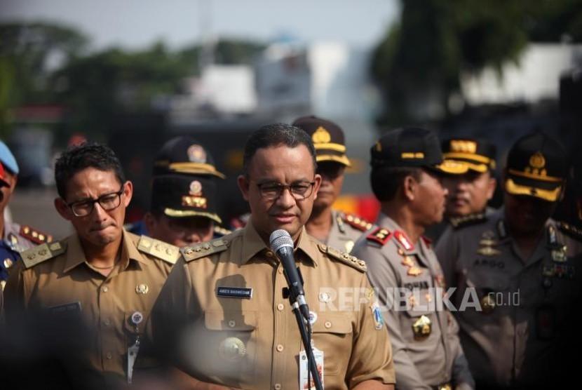 Gubernur DKI Jakarta Anies Baswedan (tengah) bersama Wakil Gubernur DKI Jakarta Sandiaga Salahudin Uno (kiri)..