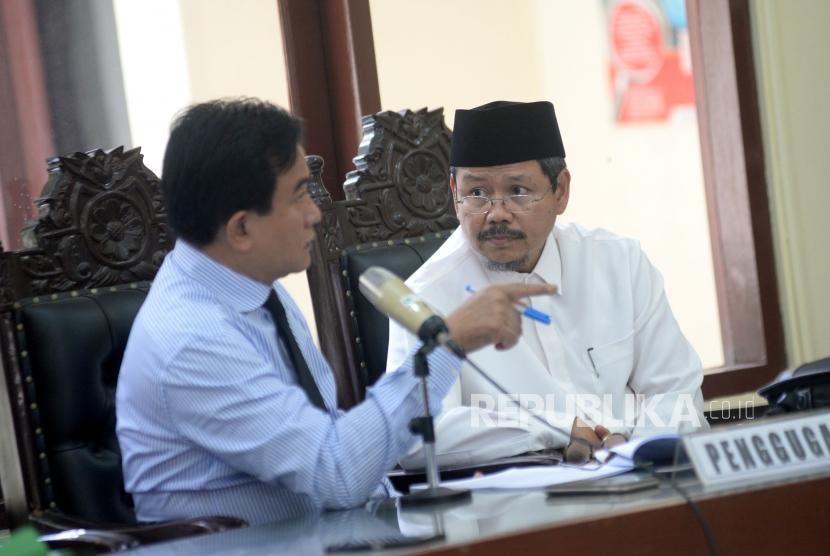 Kuasa Hukum HTI Yusril Ihza Mahendra berbincang dengan mantan juru bicara HTI Ismail Yusanto dalam sidang perdana gugatan HTI terhadap langkah pemerintah yang mencabut status badan hukumnya di PTUN Jakarta, Kamis (23/11).