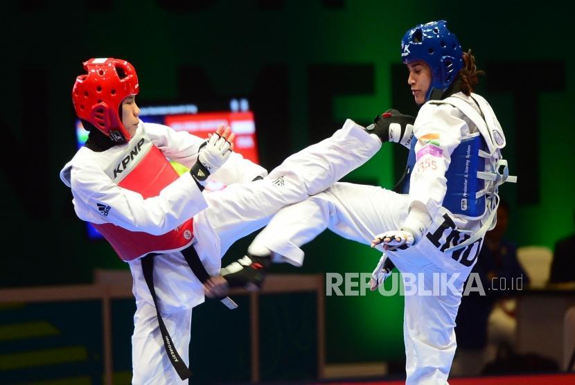 Atlet Kyorugi Taekwondo Indonesia Mariska Halinda (merah) melakukan serangan kepada lawannya Latika Bhandari (biru) dari India pada babak perempat final pertandingan Taekwondo kelas kyorugi under 53 kg, pada event Invitation Torunament Asian Games 18 di Jakarta, Sabtu (10/2).