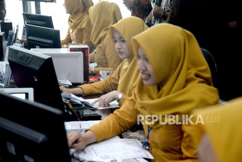 Pemanfaatan KTP-El di BPJS Kesehatan. Petugas melayani pendaftaran JKN-KIS warga menggunakan card-reader KTP Elektronik di Jakarta, Jumat (5/1).