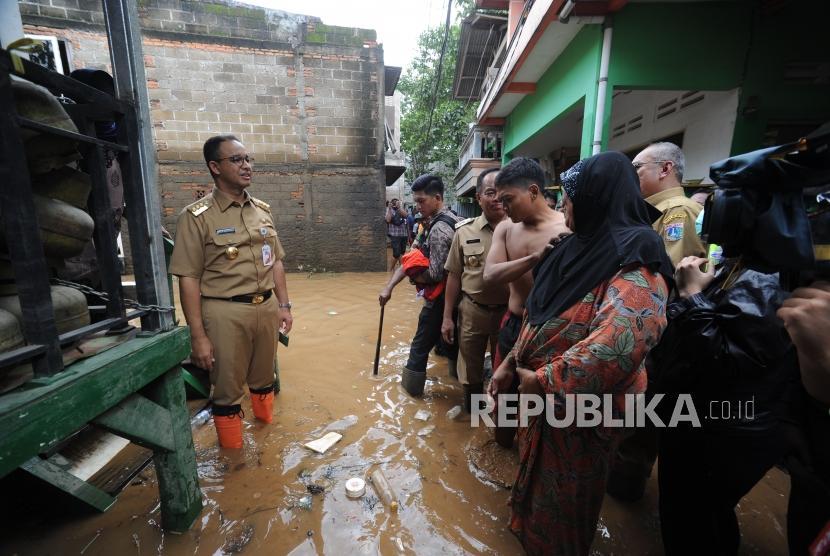Gubernur DKI Jakarta Anies Baswedan(kiri) melakukan peninjauan ke wilayah yang terkena banjir di Gang Arus, Cawang, Jakarta Timur, Selasa (6/2).