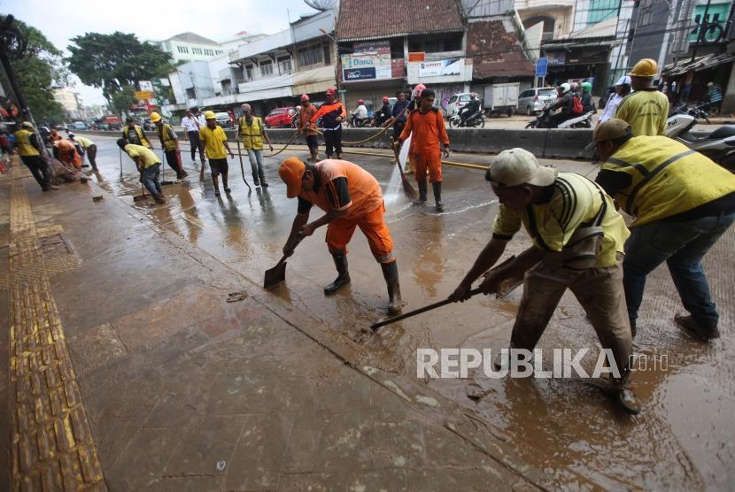 Petugas PPSU dan Bina Marga membersihkan lumpur pascabanjir di Ruas Jalan Jatinegara Barat, Jakarta, Rabu (7/2).