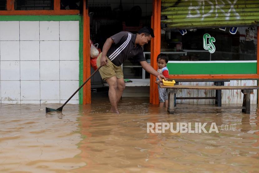 Warga beraktivitas saat banjir melanda ruas jalan Jatinegara Barat, Jakarta, Selasa(6/2).