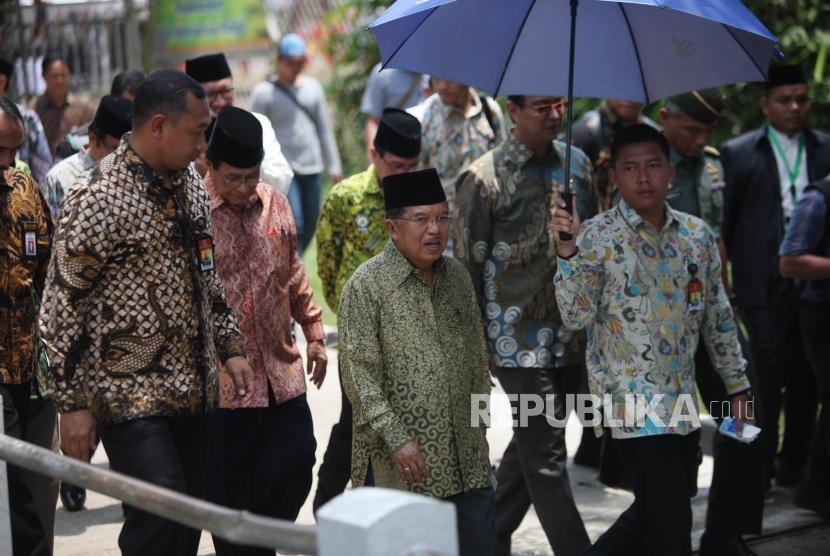 Wakil Presiden sekaligus Ketua Dewan Masjid Indonesia Jusuf Kalla (tengah) berjalan seusai pembukaan Muktamar Dewan Masjid Indonesia (DMI) ke-7.