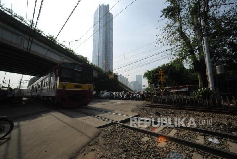 Menunggu. Pengendara kendaraan roda dua  menunggu teerbukanya pintu perlintasan kereta sebidang di Jalan K.H Mansyur, Jakarta, Rabu (1/11).
