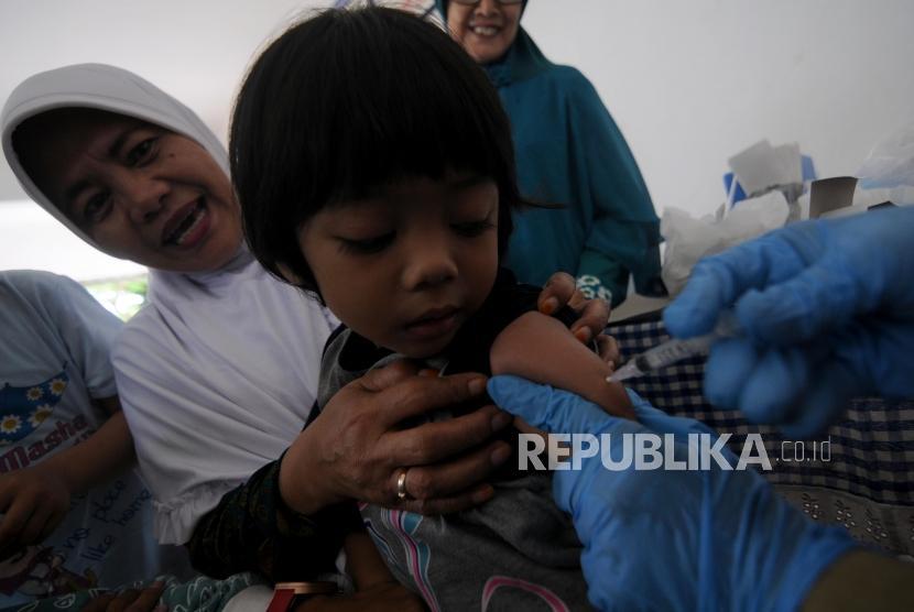 Imunisasi Massal Difteri. Seorang balita saat disuntik imunisasi Difteri di Posyandu Mawar, Pancoran Mas, Kota Depok, Jawa Barat, Senin (11/12).
