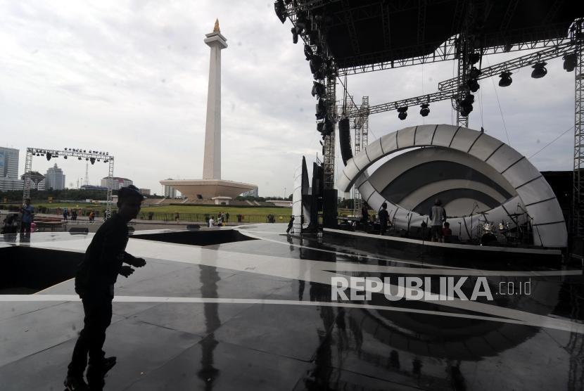 Pekerja melintasi panggung yang didirikan di kawasan Monas, Jakarta Pusat, Jumat (29/12).