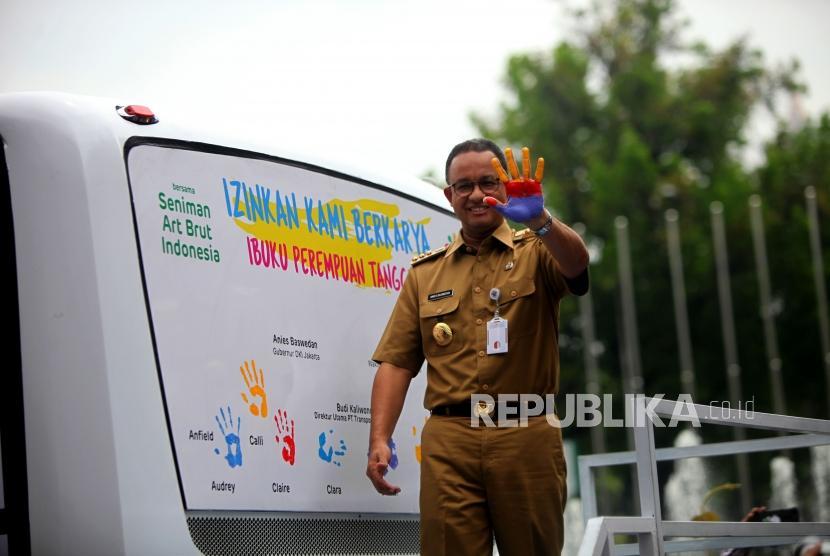 Gubernur DKI Jakarta Anies Baswedan memperlihatkan tangannya yang sudah diwarnai cat saat peresmian bus transjakarta karya anak-anak berkebutuhan khusus di Balaikota, Jakarta, Selasa (24/4).
