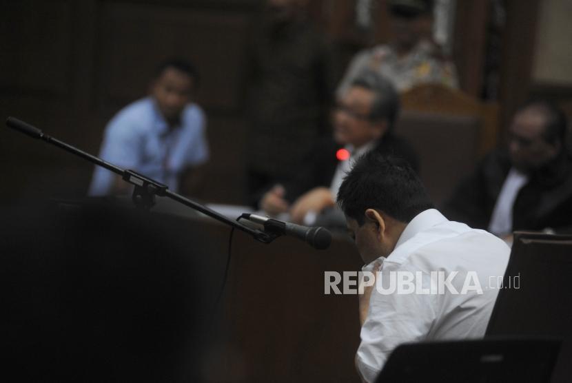 Terdakwa kasus dugaan korupsi KTP elektronik Setya Novanto duduk  tertunduk di ruangan pada sidang perdana  di gedung Pengadilan Tipikor Jakarta, Rabu (13/12).