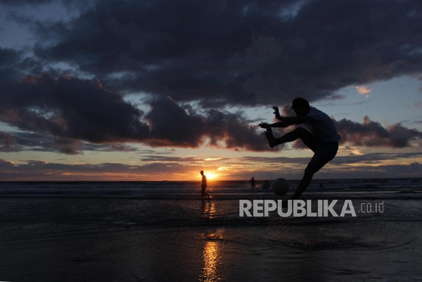 Wisatawan bermain bola di pantai Kuta, Bali, Selasa (6/2).
