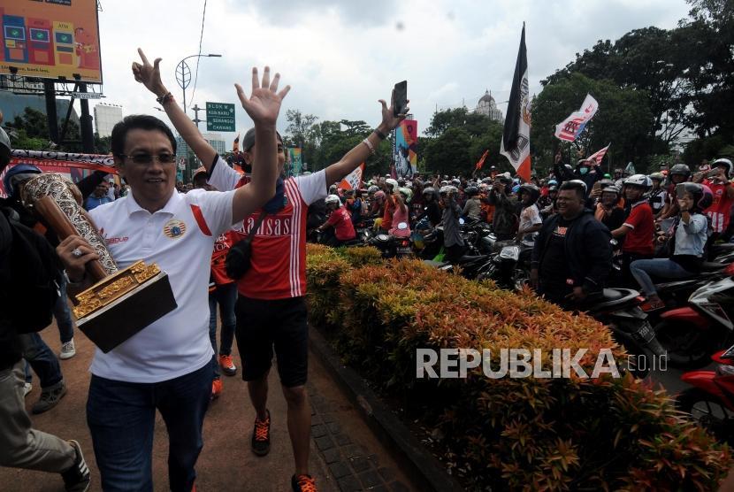 Salah satu pengurus Persija  menyapa para suporter dengan membawa trofi Piala Presiden saat akan melakukan pawai menuju Balaikota di Kawasan Senayan, Jakarta, Ahad (18/2).