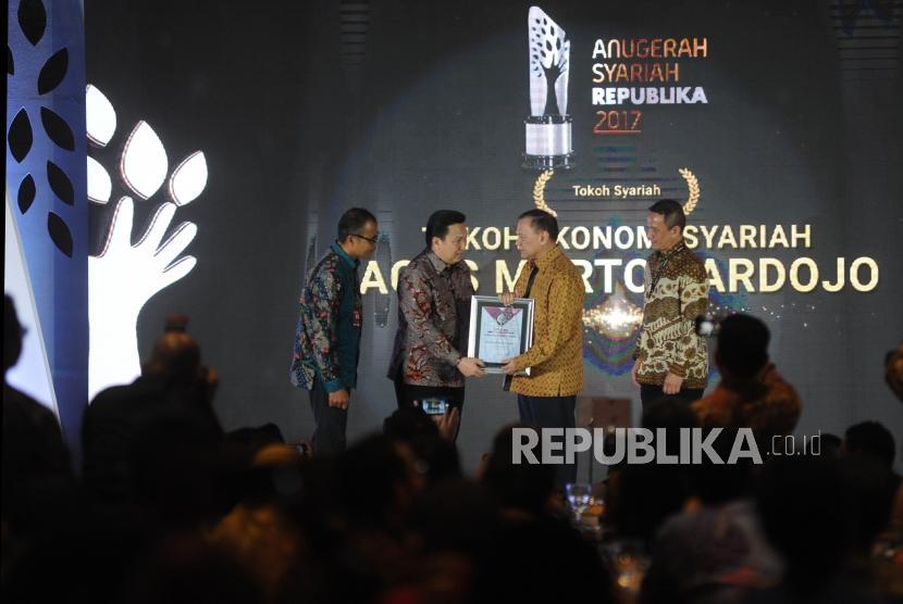 Presiden Direktur Adaro Energy Garibaldi Thohir (kedua kiri) memberikan penghargaan Tokoh Syariah kepada Gubernur BI Agus Martowardojo (kedua kanan) saat Anugerah Syariah Republika (ASR) 2017 di Jakarta, Rabu (6/12) malam.