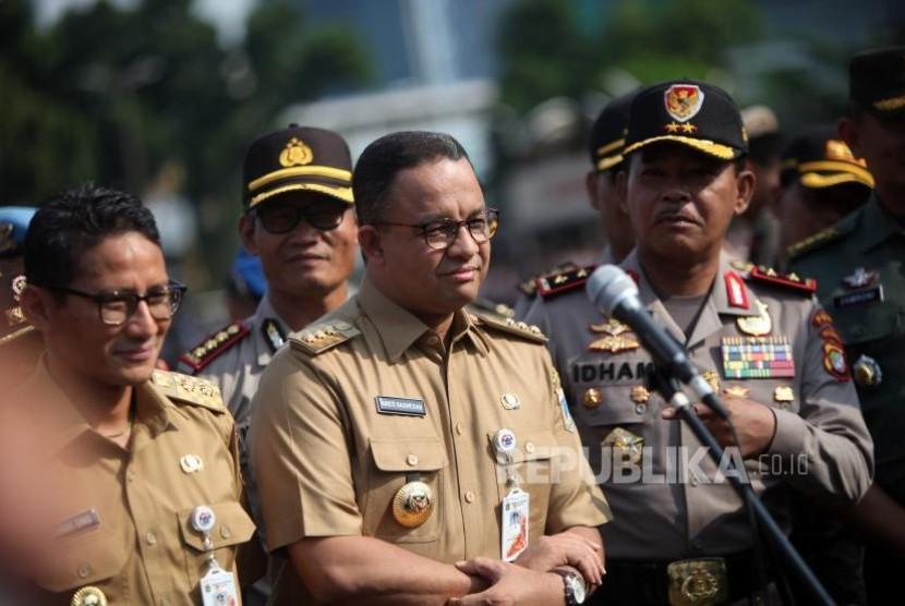 Gubernur DKI Jakarta Anies Baswedan (tengah) bersama Wakil Gubernur DKI Jakarta Sandiaga Salahudin Uno (kiri).
