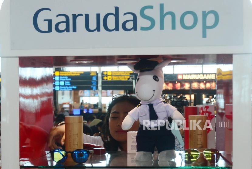 Seorang petugas GarudaShop sedang merapihkan merchandise eksklusif Garuda Indonesia disela acara peluncuran Garuda Shop JD.ID di Terminal 3 Bandara Soekarno Hatta, Cengkareng, Selasa (13/2).