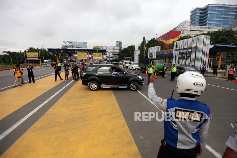 Kendaraan mobil dengan nomor polisi ganjil memutar balik saat hari pertama pemberlakuan sistem ganjil genap di Gerbang Tol Bekasi Barat 1, Bekasi, Jawa Barat, Senin (12/3).