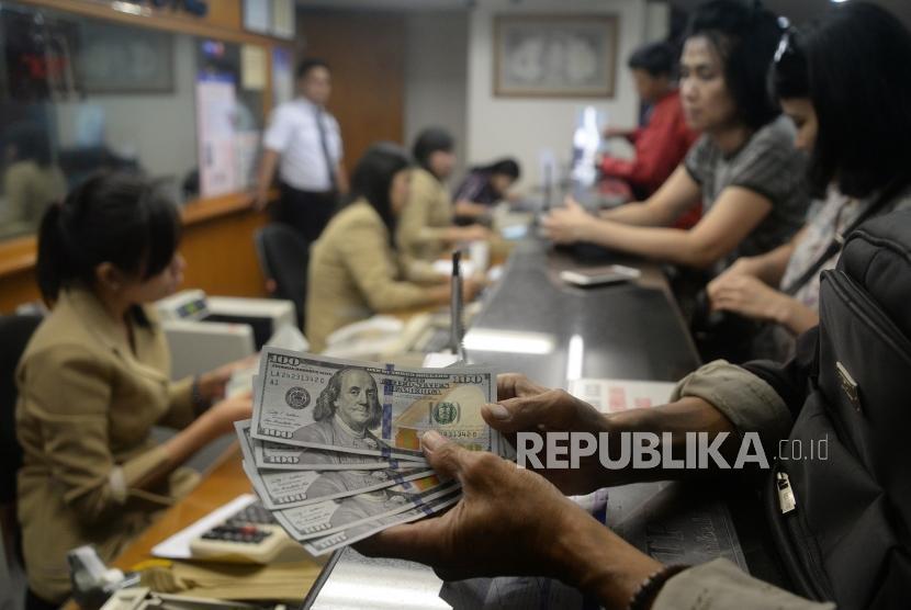 Rupiah Masih Terus Melemah. Pengunjung melakukan penukaran mata uang asing di jasa penukaran uang Ayu Masagung, Jakarta, Senin (23/4).