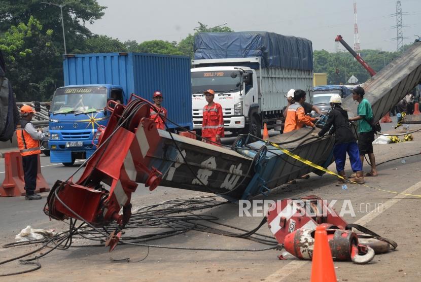 Petugas  mengevakuasi crane yang roboh di KM 15 Tol Jakarta-Cikampek di Wilayah Kota Bekasi, Jawa Barat, Kamis (16/11).