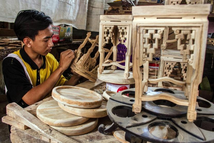 Pekerja menyelesaikan pembuatan kerajinan dekorasi rumah dari limbah mebel kayu jati di sebuah industri rumahan di Desa Klampok, Grobogan, Jawa Tengah, Jumat (24/11).