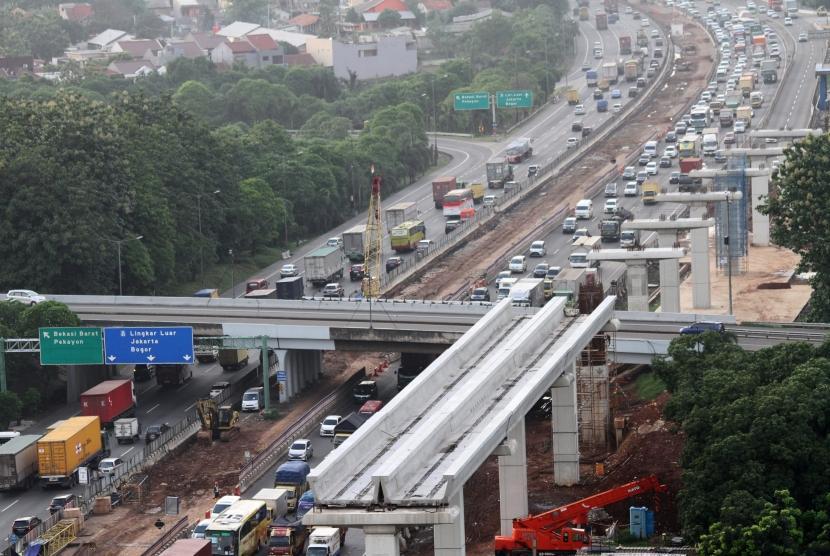 Kendaraan melintas di samping salah satu lokasi pengerjaan pembangunan infrastruktur di ruas Jalan Tol Jakarta-Cikampek, di Bekasi, Jawa Barat, Selasa (19/12).