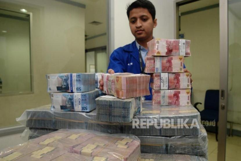 Petugas menata uang kertas rupiah di ruang penyimpanan uang