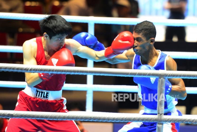 Petinju Putra Indonesia Blasius Kali Mario (biru) saling melancarkan pukulan saat berhadapan dengan petinju China Wei Tu Po saat tarung pada kelas 49 kg, di ajang Invitation Tournament Asian Games 18 di Jakarta, Ahad (11/2).
