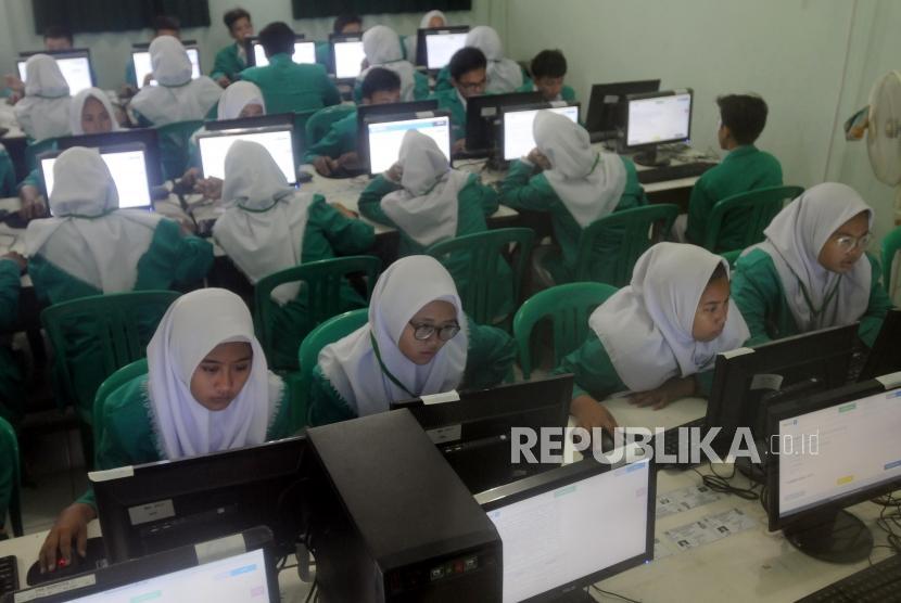 Sejumlah pelajar saat mengikuti Ujian Nasional Berbasis Komputer (UNBK) di Madrasah Tsanawiyah (MTs) Fatahillah, Jakarta, Senin (23/4).