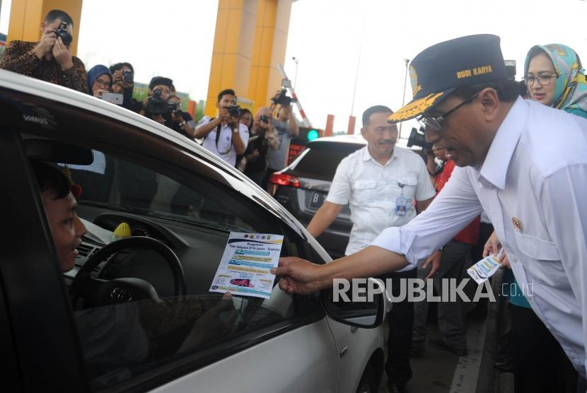 Menteri Perhubungan RI Budi Karya Sumadi  memberikan selembaran sosialisasi pengaturan kebiajakan di tol Jakarta - Tangerang kepada pengendara di pintu tol kunciran dua, Tangerang,Banten, Ahad (15/4).