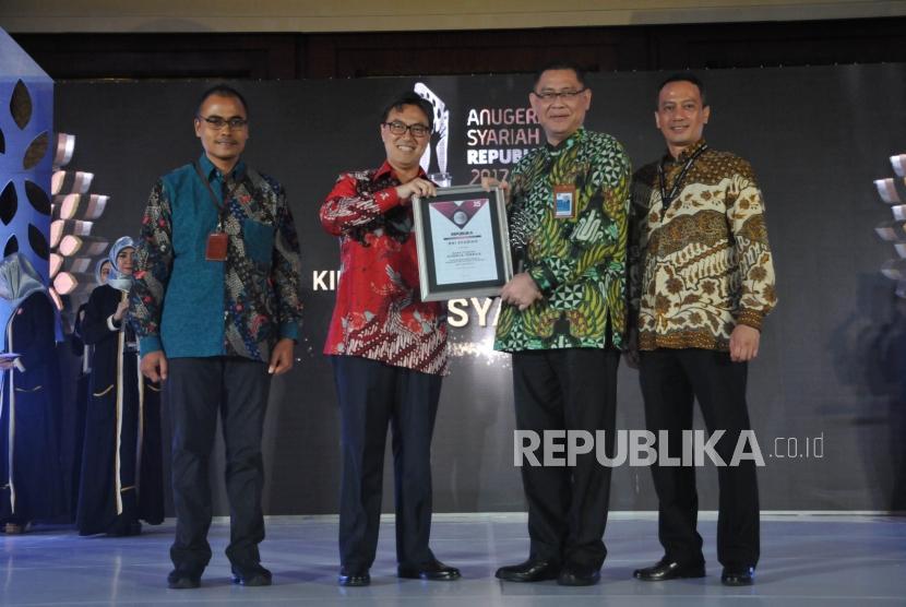 Ketua LPS Fauzi Ikhsan (kedua kiri) memberikan kepada perwakilan pemenang Bank Syariah Kinerja dan Inovasi Terbaik Aset 30 Triliun keatas kepada BNI Syariah dalam Anugerah Syariah Republika (ASR) 2017 di Jakarta, Rabu (6/12)malam.