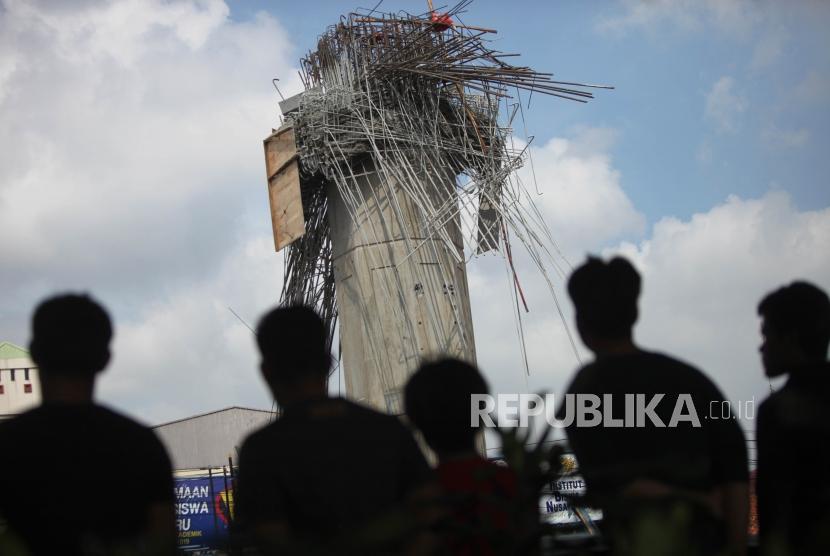 Warga menyaksikan kondisi tiang girder Tol Bekasi-Cawang-Kampung Melayu (Becakayu) yang ambruk di Jalan DI Panjaitan, Jakarta, Selasa (20/2).