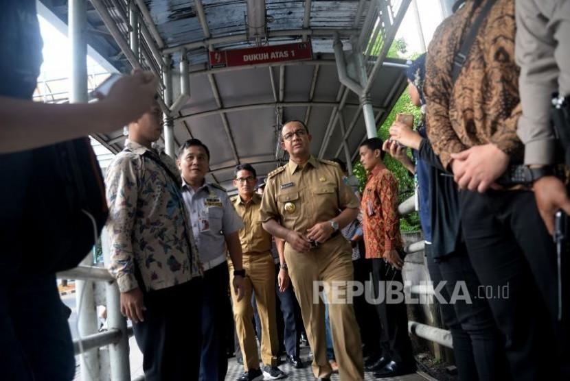 Gubernur DKI Jakarta Anies Baswedan dan Wakil Gubernur Sandiaga Uno berjalan ketika hendak menaiki bus Transjakarta di Halte Dukuh Atas, Jakarta, Selasa (17/10).