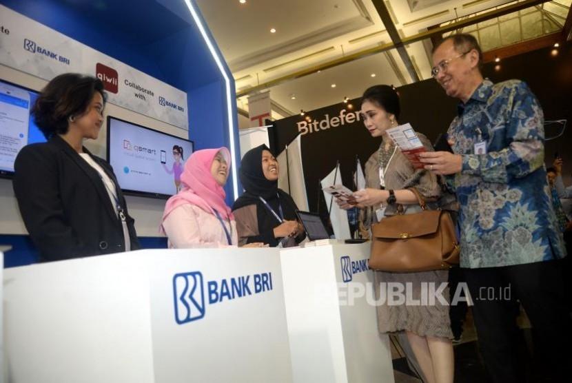 Direktur Digital Banking dan Teknologi Informasi BRI Indra Utoyo (kanan) dan Direktur Konsumer BRI Handayani (kedua kanan) berbincang dengan penjaga Stand BRI dalam pameran BRI Indocomtech 2017 di JCC, Jakarta, Rabu (1/11).
