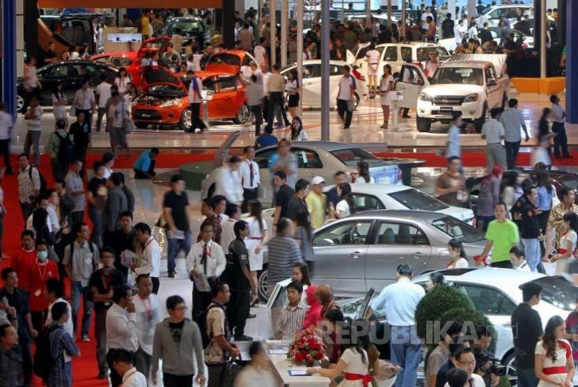 Pengunjung mengamati mobil yang dipajang pada perhelatanIndonesia International Motor Show (IIMS) ke-18 di Jakarta InternationalExpo , Kemayoran, Jumat (23/7). Pameran otomotif terbesar di tanah air ituberlangsung 23 Juli- 1 Agustus