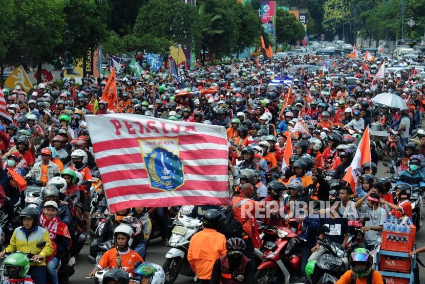 Sejumlah Suporter Persija melakukan pawai menuju Balaikota di Kawasan Senayan, Jakarta, Ahad (18/2).