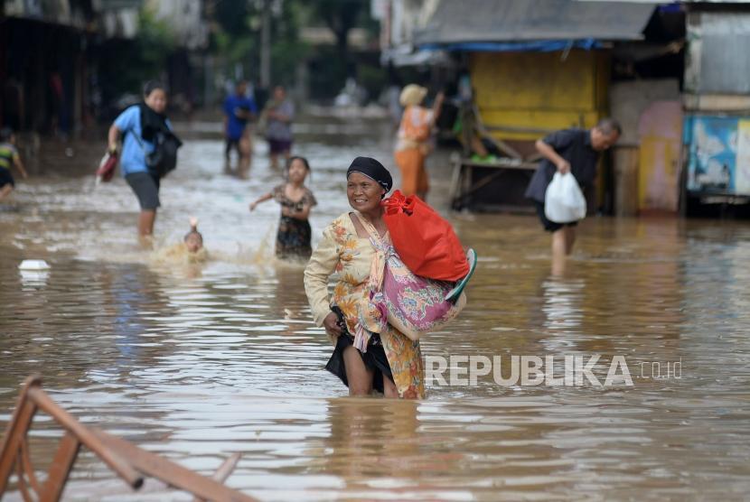 Warga melintasi genangan saat banjir melanda ruas jalan Jatinegara Barat, Jakarta, Selasa(6/2).