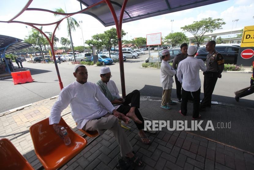 Pendukung Habib Rizieq berbincang dengan petugas polisi saat menunggu kedatangan Habib Rizieq di Bandara Soekarno-Hatta, Tangerang, Banten, Rabu (21/2).