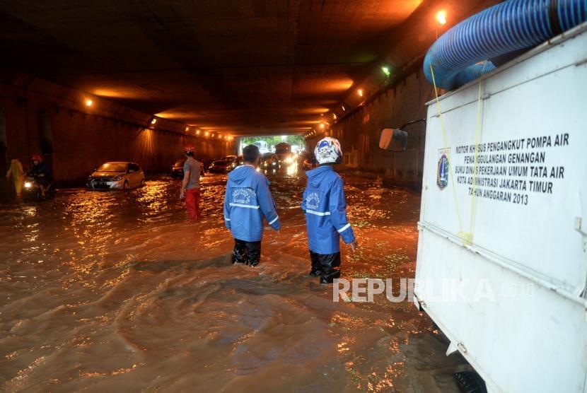 Petugas menyiapkan pompa untuk menyedot genangan air di terowongan Cawang, Jakarta, Selasa (12/12).