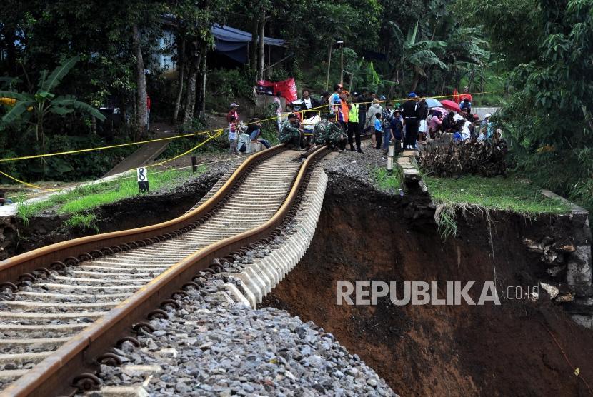 Kondisi jalur kereta api jurusan Sukabumi-Bogor yang menggantung akibat pondasi longsor di Kampung Maseng, Cijeruk, Kabupaten Bogor, Jawa Barat, Selasa (6/2).