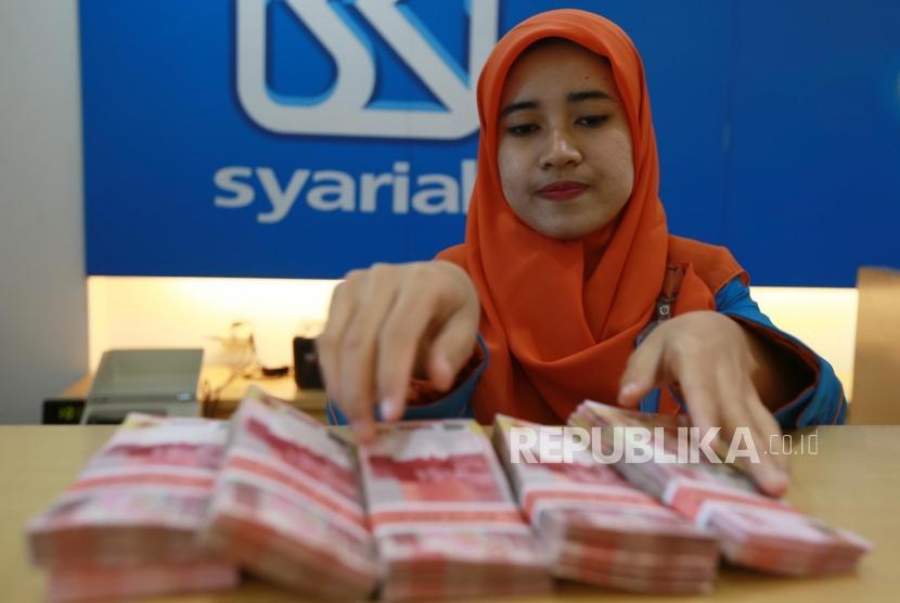 Petugas menghitung uang rupiah di Banking Hall Bank BRI Syariah, Jakarta, Kamis (30/11).