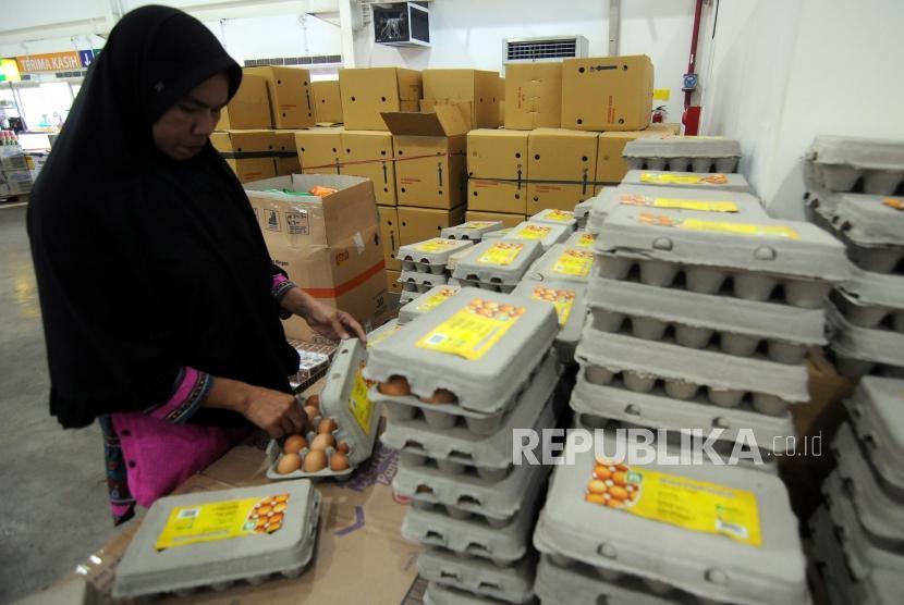 Seorang warga sedang memilih telur yang harganya terus naik menjelang Ramadhan (ilustrasi)