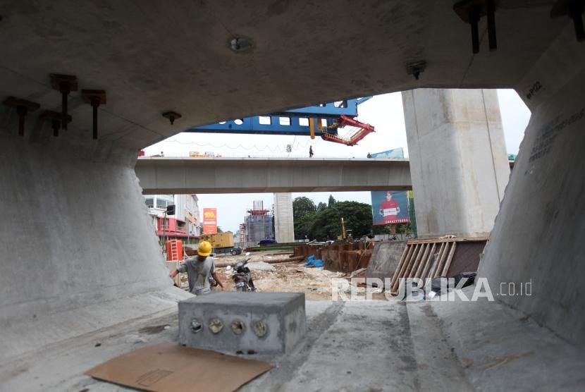 Pekerja menyelesaikan pembangunan proyek Light Rail Transit (LRT) Atau kereta api ringan dikawasan Kelapa Gading, Jakarta, Ahad (14/1).