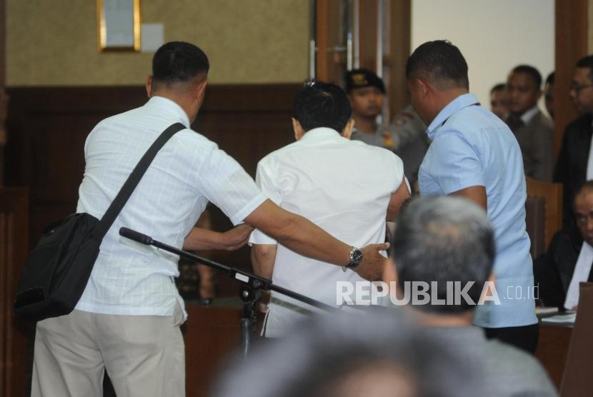 Terdakwa kasus dugaan korupsi KTP elektronik Setya Novanto (Tengah) di boyong keluar ruangan pada sidang perdana  di gedung Pengadilan Tipikor Jakarta, Rabu (13/12).