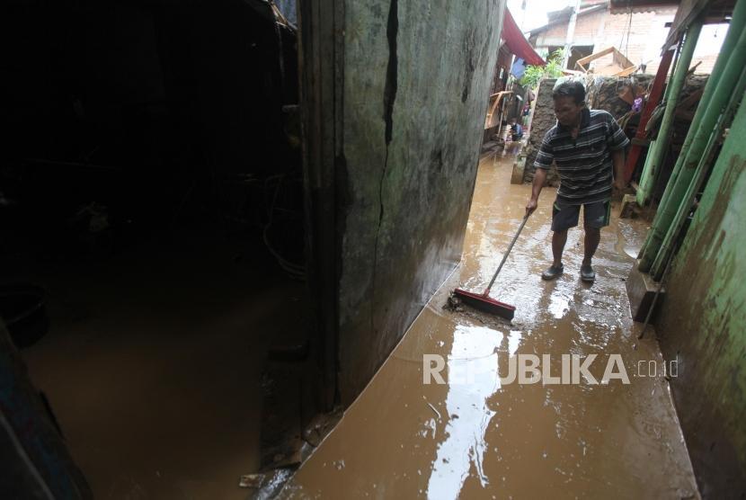Warga membersihkan rumahnya dari lumpur pasca banjir di Kawasan Rawajati, Jakarta, Selasa (6/2).