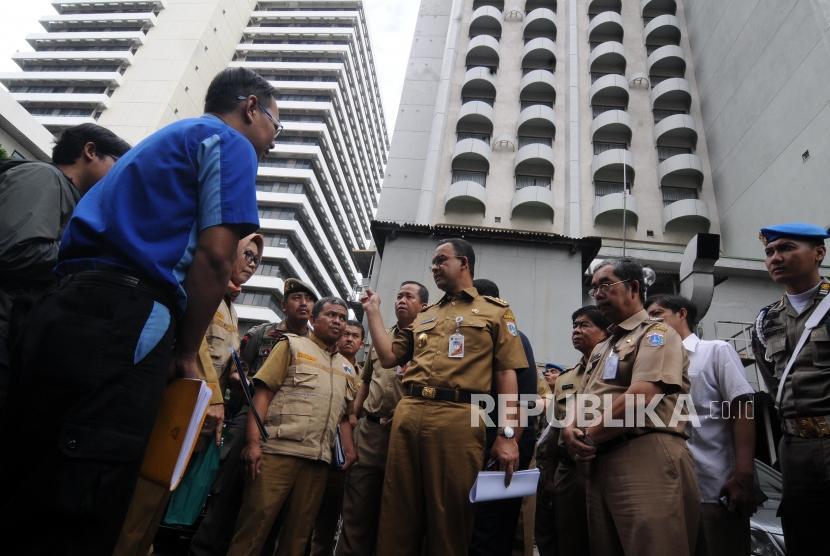 Gubernur DKI Jakarta Anies Baswedan (tengah) didampingi Tim Pengawasan Terpadu Sumur Resapan Instalasi Pengelolaan Air Limbah dan Air Tanah saat melakukan sidak di Hotel Sari Pan Pacific, Thamrin, Jakarta, Senin (12/3).